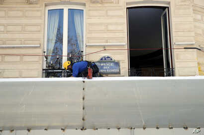 A worker sets up protections on the famed restaurant Fouquet's of the Champs Elysees, in Paris, March 22, 2019. French President Emmanuel Macron has announced that soldiers will be deployed across the country to help maintain security during yellow v...