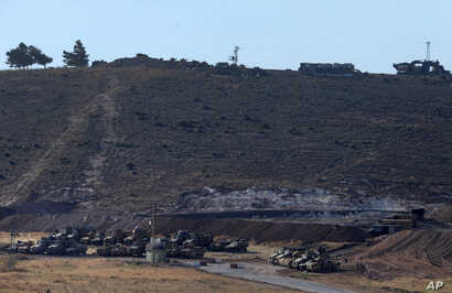 Turkey's tanks and vehicles hold positions close to the border with Syria, Oct. 9, 2017. Turkey's military said Monday that Turkish troops moved into Syria's northwestern Idlib province as part of an operation to enforce a de-escalation zone that was...