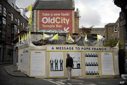 A passerby looks at an art installation protesting the pope's visit, in Dublin, Ireland, Aug. 24, 2018.