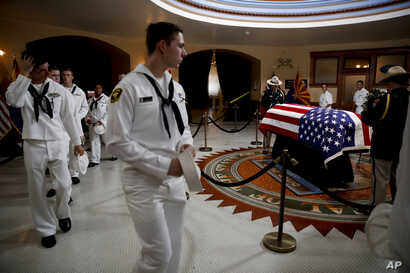 U.S. Naval sea cadets walk past the casket to pay their respects to Sen. John McCain, R-Ariz. at the Arizona Capitol in Phoenix, Aug. 29, 2018.