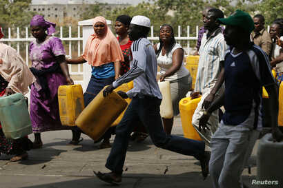 "A man breaks out of the queue as he rushes to a kerosene cooking fuel pump during the launch of the ""kero correct"" scheme at a Nigerian National Petroleum Corporation (NNPC) mega petrol station in Abuja, Jan. 23, 2015."