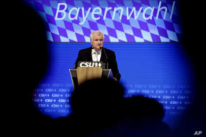 FILE - German Interior Minister and chairman of the German Christian Social Union party Horst Seehofer delivers a speech at a party convention of the CSU in Munich, Germany, Sept. 15, 2018.