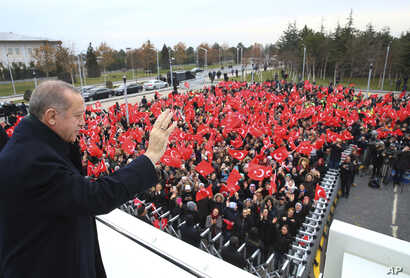Turkey's President Recep Tayyip Erdogan waves to a group of workers at the airport in Ankara, Turkey, Dec. 7, 2017 prior to his departure on a two-day official visit to Greece.