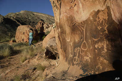 In this May 26, 2017, photo, Susie Gelbart walks near petroglyphs at the Gold Butte National Monument near Bunkerville, Nev. The monument is along the Arizona border in Southern Nevada.