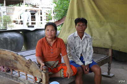 Keo Eat, 52, a deputy Prey Khla commune chief, decided to join the ruling Cambodian People's Party after being served with a court summons shortly before the deadline to defect. He's shown with his wife, Keo Sarin.