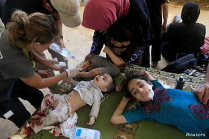 FILE - Wounded and displaced Iraqi children who fled from clashes receive treatment in western Mosul, Iraq, June 3, 2017.