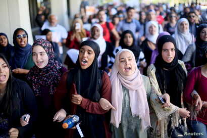 FILE - Students chant while marching at a rally against Islamophobia at San Diego State University in San Diego, California, Nov. 23, 2015.