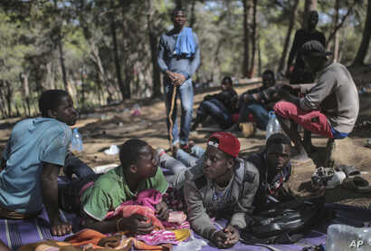 Sub-Saharan migrants aiming to cross to Europe take shelter in a forest overlooking the neighborhood of Masnana, on the outskirts of Tangier, Morocco, Sept. 5, 2018.