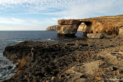 Tourists walk near the Azure Window, a 50 metre high rock arch, at Dwejra Point cliffs on the west coast of the Maltese island of Gozo, Sept. 23, 2016.