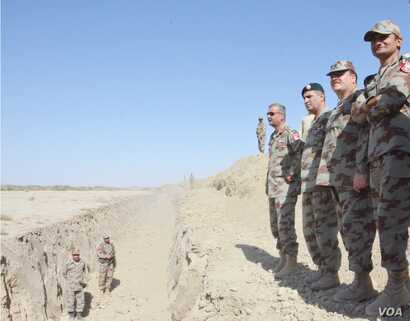 Pakistan army officers survey the trench near the border with Afghanistan.