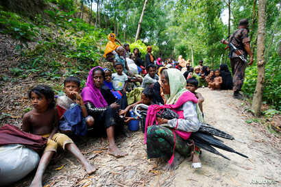 Rohingya people sits on the Bangladesh side as they are restricted by the members of Border Guards Bangladesh (BGB), to go further inside Bangladesh, in Cox's Bazar, Bangladesh, Aug. 28, 2017.