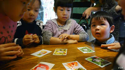 In JUCCCE's New Way to Eat program, a card game encourages Chinese children to eat a plant-based diet. They're shown at Sproutworks, a Shanghai salad and sandwich shop. (Photo courtesy of JUCCCE)