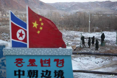 """FILE - A Chinese-built fence near a concrete marker depicting the North Korean and Chinese national flags with the words """"China North Korea Border"""" at a crossing in the Chinese border town of Tumen in eastern China's Jilin province."""
