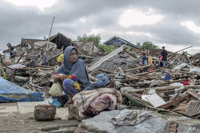 A tsunami survivor sits on debris as she salvages items from the location of her house in Sumur, Indonesia, Dec. 24, 2018.