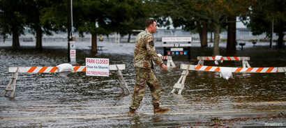 An Army member walks near the flooded Union Point Park Complex as the Hurricane Florence comes ashore in New Bern, North Carolina, Sept. 13, 2018.