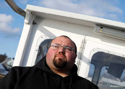Lobsterman Drew Eaton, 27, stands aboard his boat in Stonington, Maine, Dec. 11, 2017.