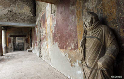 FILE- A damaged statue is seen in the Thermae Stabianae in Pompeii, Italy, March 8, 2012.