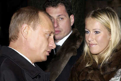 FILE - Russian President Vladimir Putin, left, speaks to Ksenia Sobchak, daughter of former St. Petersburg mayor Anatoly Sobchak at a cemetery in St. Petersburg, Russia, Nov. 29, 2003.