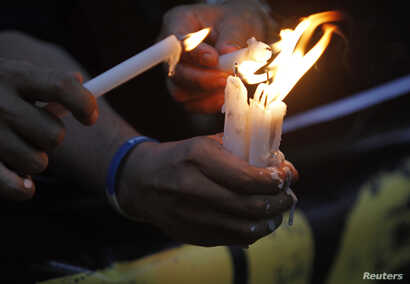 FILE - Filipino photojournalists light candles to commemorate the first anniversary of the killings in Maguindanao in southern Philippines during a protest rally in Manila, Nov. 23, 2010.