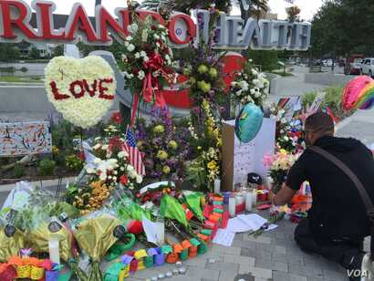 People leave flowers and other items at a makeshift vigil outside the Orlando Regional Medical Center, which is close to where the mass shooting occurred at the Pulse gay nightclub early Sunday in Orlando, Florida, June 14, 2016.