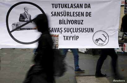 """A woman walks past a banner picturing Turkish President Recep Tayyip Erdogan that reads, """"When you arrest (journalists) or censor (media) we know that you are a war criminal, Tayyip,"""" during a protest over the arrest of journalists Can Dundar and Erd..."""