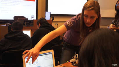 Allison Zubeck, a freshman studying industrial and systems engineering at USC helps school age students during a robotics workshop at the USC robotics open house.
