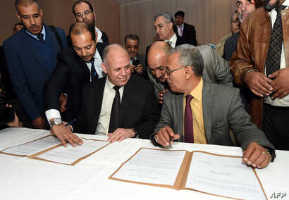 Awad Mohammed Abdul-Sadiq (L), the first deputy head of the Tripoli-based General National Congress (GNC), and Ibrahim Fethi Amish from the internationally recognised House of Representatives sign documents after reaching an agreement on ending the p