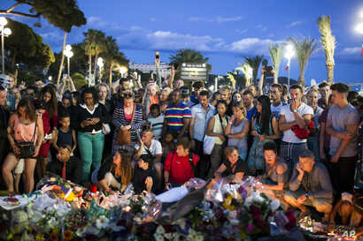 People gather at a makeshift memorial to honor the victims of an attack, near the area where a truck mowed through revelers in Nice, southern France, Friday, July 15, 2016.