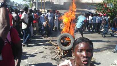 Protesters set fire to tires, blocking a street in downtown Port au Prince, Haiti on Nov 18, 2018.