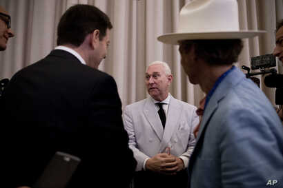 FILE - In this photo taken July 16, 2016, Roger Stone, an adviser to Donald Trump, center, speaks to reporters in New York. Stone says he believes his contacts with a Russian-linked hacker who took credit for breaching the Democratic National Committ...