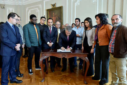 Colombian President Ivan Duque signs the financing agreement for public education accompanied by the student leaders in the presidential palace of Bogota, Colombia, Dec. 14, 2018.