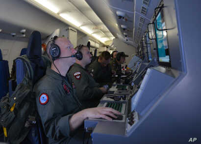 In this photo provided by the U.S. Navy, crew members on board an aircraft P-8A Poseidon assist in search and rescue operations for Malaysia Airlines flight MH370 in the Indian Ocean on Sunday, March 16, 2014. Malaysian authorities on Sunday examined...