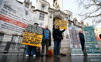 Pro and anti-Brexit protesters stand outside the Supreme Court on the third day of the challenge against a court ruling that Theresa May's government requires parliamentary approval to start the process of leaving the European Union, in Parliament Sq...