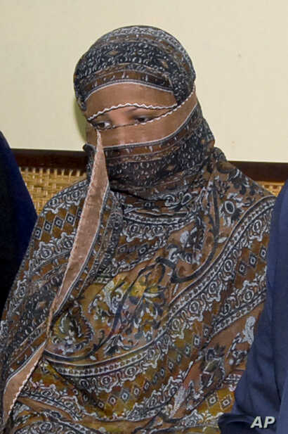 Pakistani Christian woman Asia Bibi, listens to Governor of Pakistani Punjab Province Salman Taseer, unseen, at a prison in Sheikhupura near Lahore, Nov. 20, 2010.
