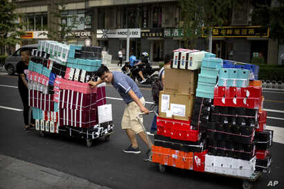 FILE - Workers pull carts loaded with shoes made by Nike and other Chinese and foreign shoe manufacturers along a street in Beijing.