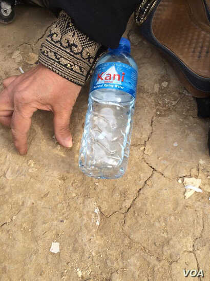 Not wanting to show her face on camera for fear of IS-violence against her family, grandmother Haifa Hamid makes a map of New Mosul with a water bottle, demonstrating where entire blocks have been flattened on March 26, 2017 in Hammam Alil, Iraq. (H....