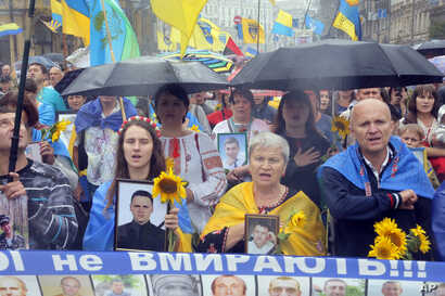 FILE - People hold photos of Ukrainian soldiers killed in the conflict with Russia-backed separatists in Ukraine's east, at a rally in Kyiv, Aug. 24, 2016.