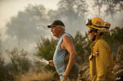 Jim Berglund sprays water while defending his home as a wildfire approaches, July 8, 2017, near Oroville, Calif.  Although flames leveled Berglund's barn, his home remained unscathed as the fire passed.