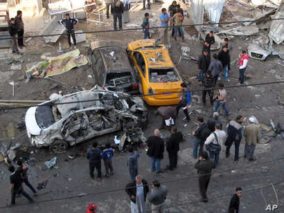 Civilians gather at the site of a car bomb attack at an outdoor market in Baghdad, Jan. 20, 2014.