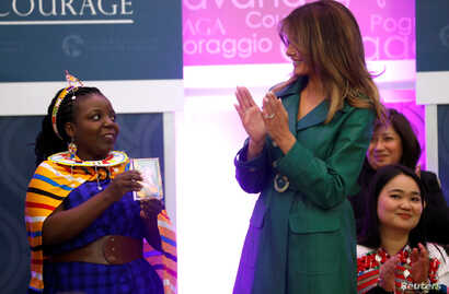 First lady Melania Trump gives an award to Tanzanian lawyer Anna Henga during the International Women of Courage (IWOC) celebration at the State Department in Washington, U.S., March 7, 2019.