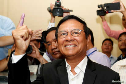 FILE - Kem Sokha, president of the opposition Cambodia National Rescue Party, casts his vote during local elections in Kandal province, Cambodia, June 4, 2017. Kem Sokha was charged with treason in early September, accused of colluding with a foreign...