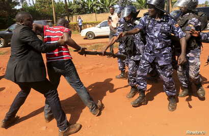 A supporter of Uganda's former Prime Minister Amama Mbabazi wrestles with the gun of a policeman, as riot police disperse a gathering in Jinja town in eastern Uganda September 10, 2015.