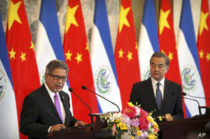 El Salvador's Foreign Minister Carlos Castaneda, left, speaks as China's Foreign Minister Wang Yi listens at a signing ceremony to mark the establishment of diplomatic relations between El Salvador and China at the Diaoyutai State Guesthouse in Beiji...
