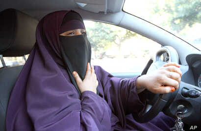 File - Kenza Drider, wearing a niqab, drives a car in Avignon, southern France.