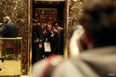 Two women smile at the press pool from the elevator at Trump Tower in New York, Dec. 12, 2016. (R. Taylor/VOA)