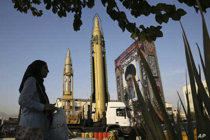 A Ghadr-H missle, center, a solid-fuel surface-to-surface Sejjil missile and a portrait of the Supreme Leader Ayatollah Ali Khamenei are on display for the annual Defense Week, at Baharestan Square in Tehran, Iran, Sept. 24, 2017. Iran's elite Revolu...