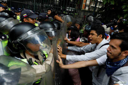 Opposition supporters confront riot security forces while rallying against President Nicolas Maduro in Caracas, Venezuela, May 12, 2017.