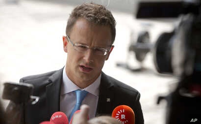 FILE - Hungarian Foreign Minister Peter Szijjarto speaks with the media as he arrives for a meeting of EU foreign ministers at the EU Council building in Luxembourg, Sept. 4, 2015