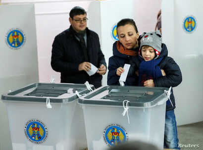 People cast ballots during a presidential election at a polling station in Chisinau, Moldova, Nov. 13, 2016.
