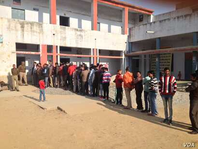Voters wait in long lines outside schools and colleges that have been turned into polling stations will deliver a crucial verdict on the popularity of Prime Minister Narendra Modi half way through his term. (A. Pasricha/VOA)